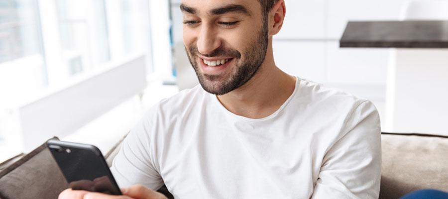 jeune qui sourit devant smartphone